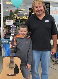 Nikki M. with Marc Rines and the Fender FA100 guitar his family won